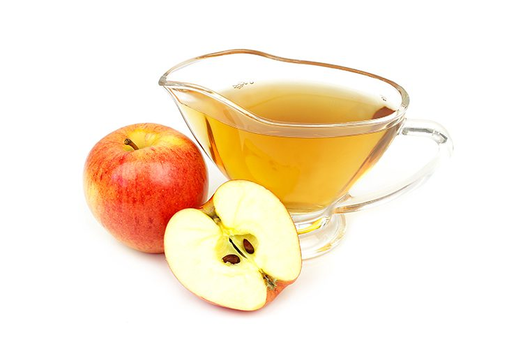 A glass of apple cider vinegar with apples