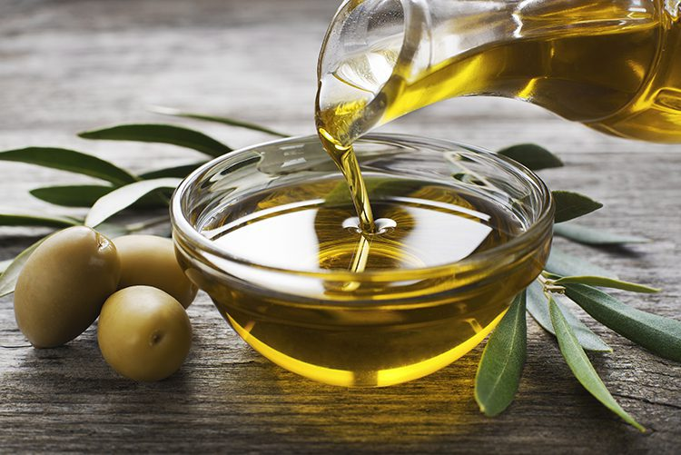 A bottle of olive oil pouring into a bowl surrounded by olives