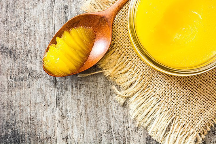 A jar of butter with a spoon of ghee
