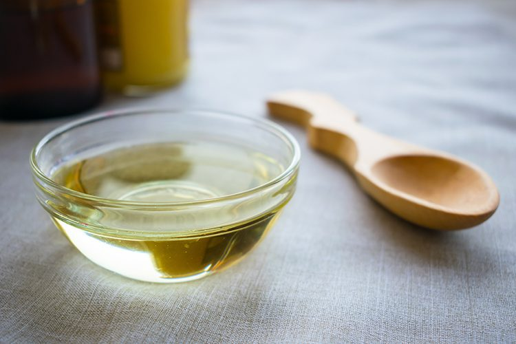 A bowl of MCT oil with a wooden spoon