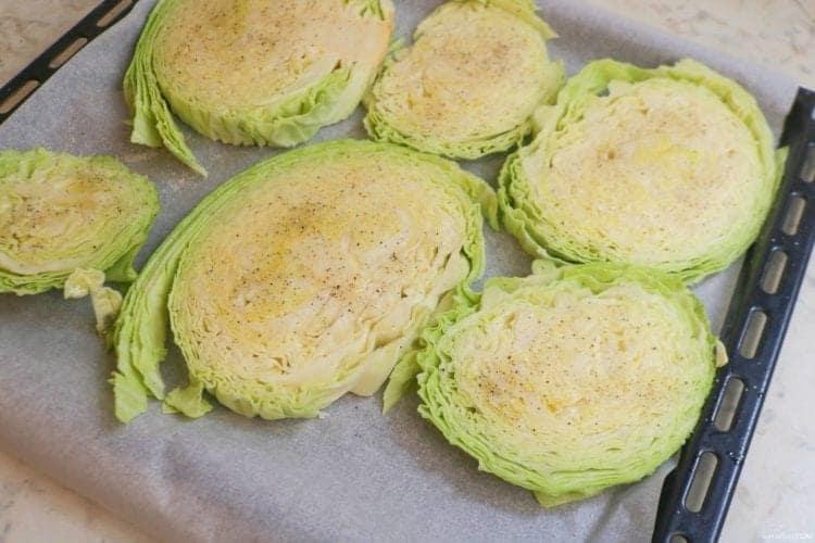 Seasoning the cabbage steaks before roasting
