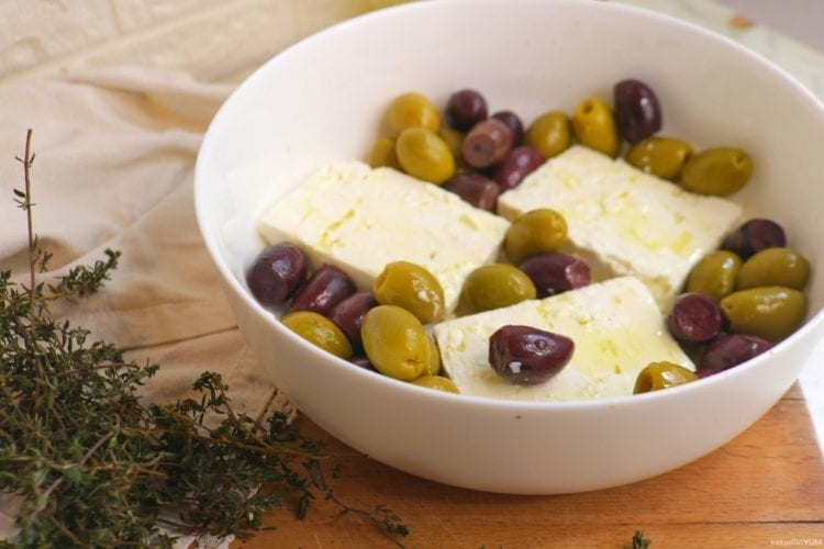 Sliced feta cheese and olives in a baking dish
