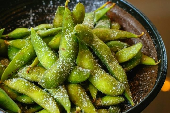 A bowl of edamame in the pod with parmesan cheese