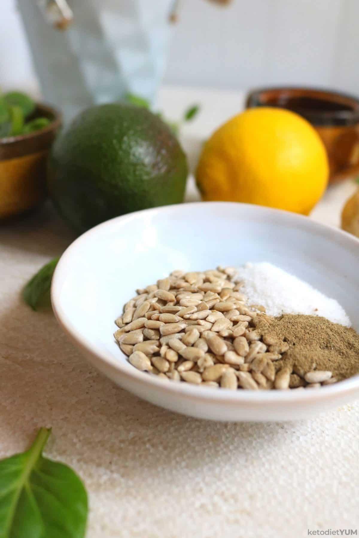 A bowl of sunflower seeds, salt and black pepper